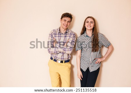 Smiling happy loving couple in casuals standing in empty room - indoors - stock photo