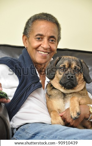 Smiling Happy Mature Woman with Gray short Afro Hairstyle holding pet dog Looking at Camera - stock photo