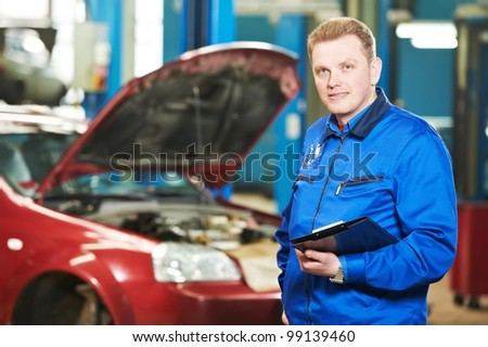 Smiling happy mechanic technician inspector foreman with clipboard at car maintenance repair service station - stock photo