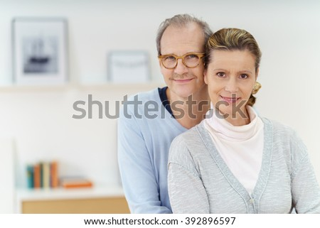 Smiling happy middle aged couple posing in a close embrace lloking at the camera with friendly smiles, with copy space to the side