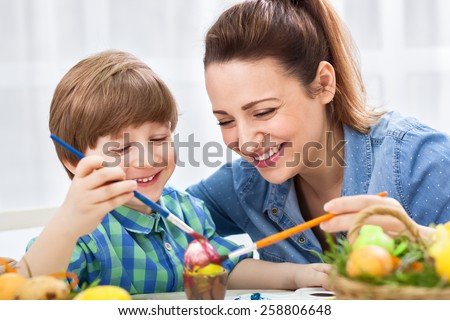 Smiling happy mother and child painting easter eggs - stock photo