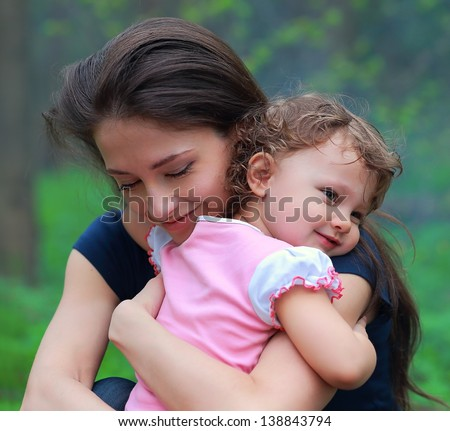 Smiling happy mother and cute kid girl cuddling outdoor summer background. Closeup tender and love portrait - stock photo