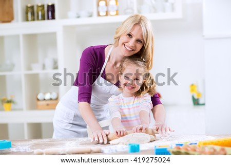 Smiling happy mother and daughter knead the dough in the kitchen - stock photo