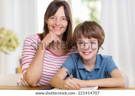 Smiling happy mother and young son sitting close together at the dining table working on paperwork or homework from school