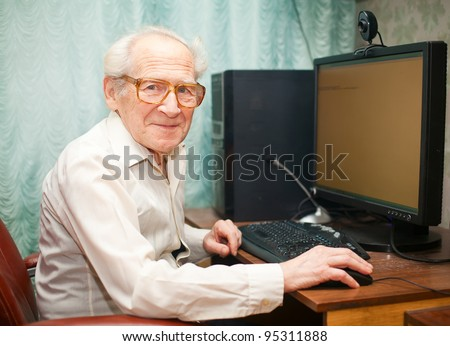smiling happy old man sitting near computer and holding mouse - stock photo