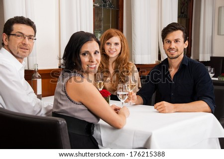 smiling happy people friends in restaurant for dinner  - stock photo