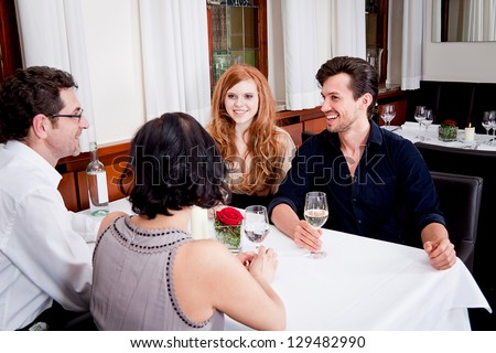 smiling happy people in restaurant drinking talking having fun