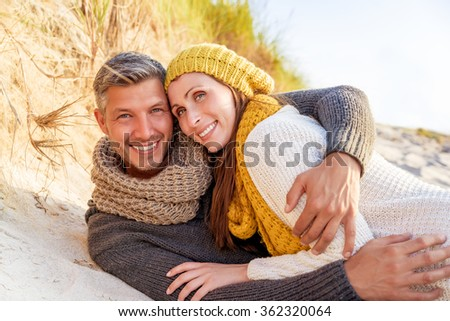 smiling happy relaxed romantic couple in the sand in spring - stock photo