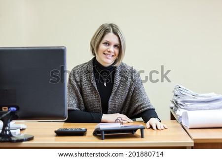 Smiling happy secretary at the table looking at camera - stock photo