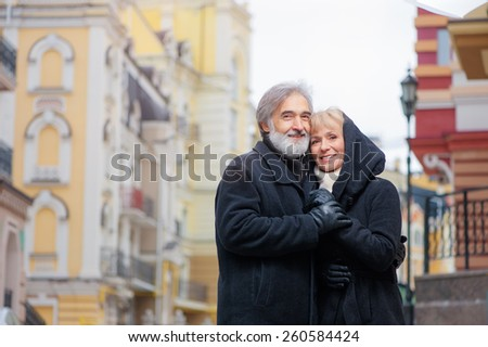 Smiling happy senior couple wearing coats in the city - stock photo