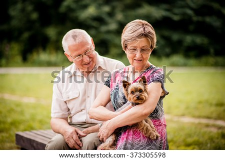 Smiling happy senior couple with their dog pet outdoor in nature