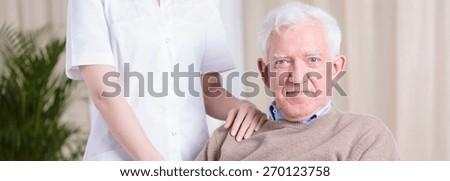 Smiling happy senior man and nurse - panorama - stock photo