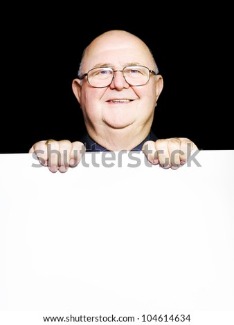 Smiling happy senior man with glasses, standing behind blank white board on black background in a pensioner savings and discount deals conceptual - stock photo