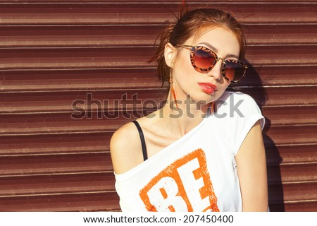 smiling happy sexy girl sitting near the wall in sunglasses redhead with big full lips - stock photo