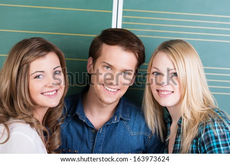 Smiling happy teenage boy and girls posing close together in front of the blackboard in the classroom as they take a break from college classes - stock photo