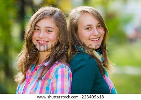 Smiling happy teenager girls having fun outdoors - stock photo