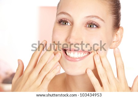 Smiling happy woman feeling her pure skin with her fingers