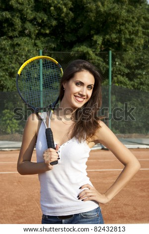 Smiling happy woman on tennis court with racket. Healthy lifestyle