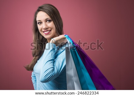 Smiling happy woman shopping with lots of colorful bags