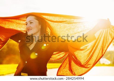 Smiling happy woman with long brown fluttering scarf on sunset - stock photo