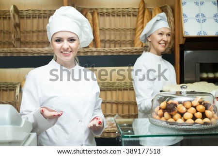smiling happy women in hats posing in bakery with baguettes and buns - stock photo