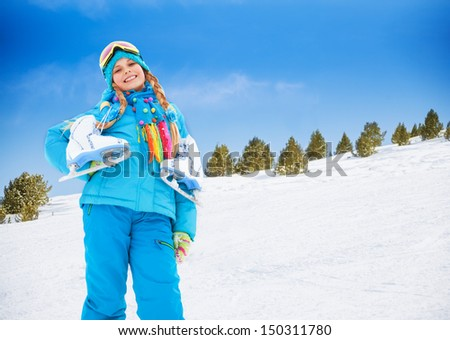 Smiling happy 10 years old Caucasian girl standing with ice-skates outside on winter day - stock photo