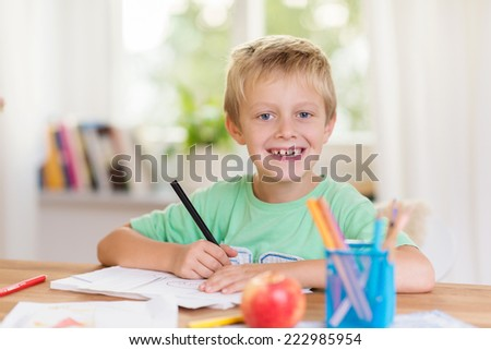 Smiling happy young boy doing schoolwork sitting at a table writing in a notebook and looking at the camera with a cheeky grin - stock photo