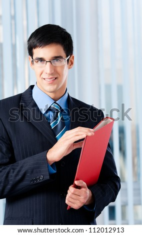 Smiling happy young business man with red folder, at office