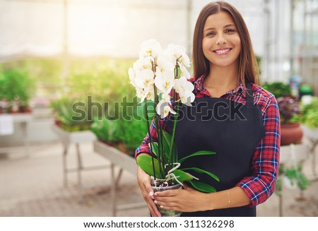 Smiling happy young florist in her nursery standing holding a potted white Phalaenopsis orchid plant in her hands as she tends to the houseplants in the greenhouse - stock photo