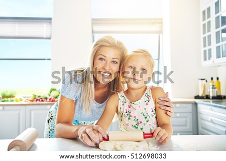 Smiling happy young mother and daughter learning to bake posing arm in arm at the kitchen counter