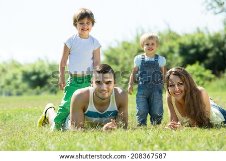 Smiling happy young parents with children laying in summer grass