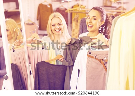 Smiling happy young woman shopping jersey at the apparel store