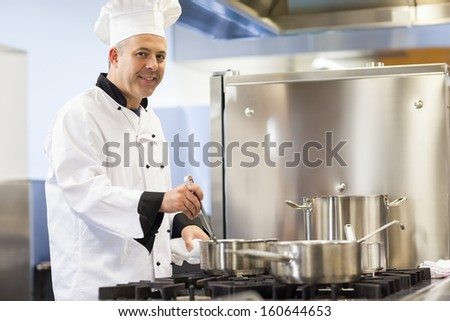 Smiling head chef stirring in pot in professional kitchen