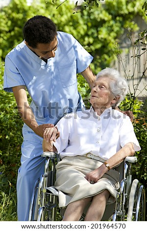 smiling health care worker talking to senior handicapped patient  outdoors , holding her hand - stock photo