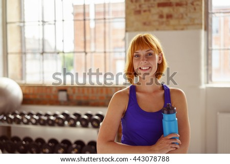 Smiling healthy attractive young woman in a gym standing holding a flask of water or energy drink smiling happily at the camera, with copy space - stock photo