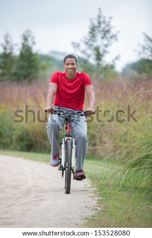 Smiling Healthy Looking Young African American Biking Outdoor