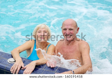 Smiling healthy senior couple having fun together in the swimming pool enjoying jacuzzi  - stock photo