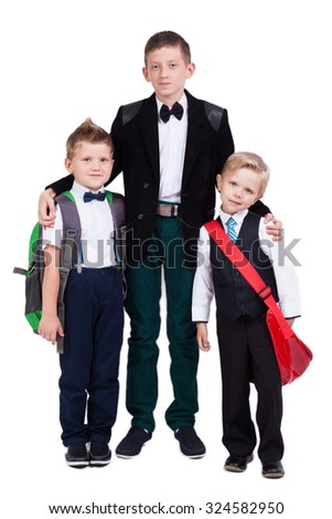 smiling high school student and two cute kid with a backpack on a white background looking at the camera, picture with depth of field - stock photo