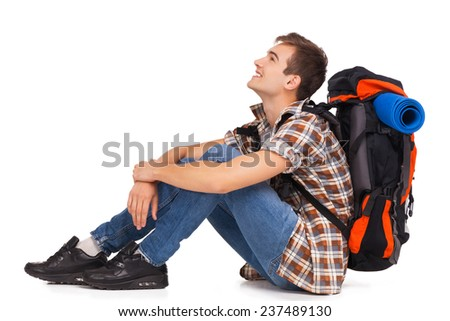 Smiling hiker sitting with knapsack - stock photo
