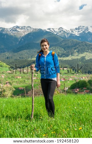 Smiling hiking young woman with backpack and woodstick as trekking poles on the mountain trail - stock photo
