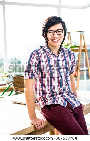 Smiling hipster businessman posing for camera in office