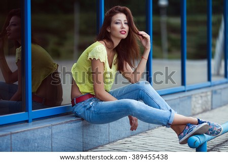 Smiling hipster girl in blue jeans in the summer city. Modern youth lifestyle concept. Outdoor shot - stock photo