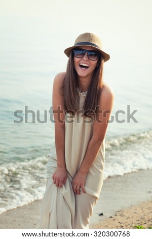 Smiling hipster girl walking on a sea beach. - stock photo