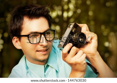 Smiling Hipster Man in Glasses Taking a Photo with Vintage Camera - stock photo