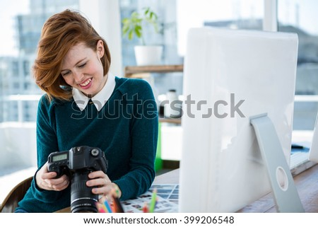 smiling hipster photographer, sitting at her desk, looking t her camera - stock photo