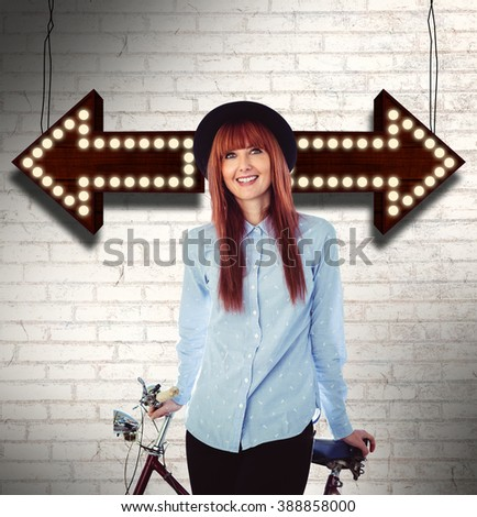 Smiling hipster woman leaning on a bike against white wall - stock photo