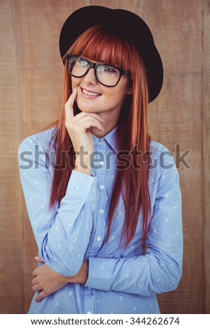 Smiling hipster woman posing face to the camera against wooden background - stock photo