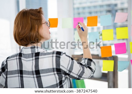 smiling hipster woman sticking notes on a notice board in office - stock photo