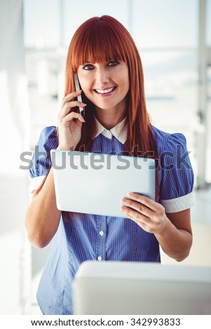 Smiling hipster woman with tablet phoning in her office