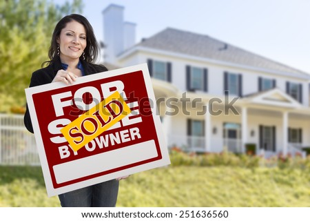 Smiling Hispanic Female Holding Sold For Sale By Owner Sign In Front of Beautiful House. - stock photo